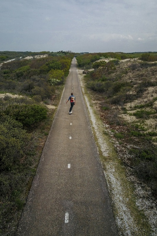 Aerial man on skateboard on an isolated straight empty road