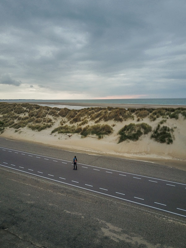 A man on a skateboard by the sea, aerial photo