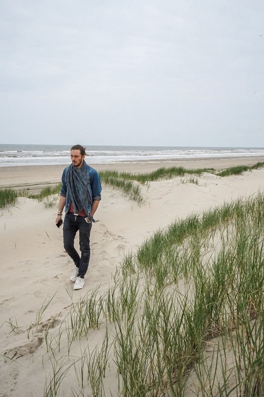 Man walks on his own by the beach on overcast day