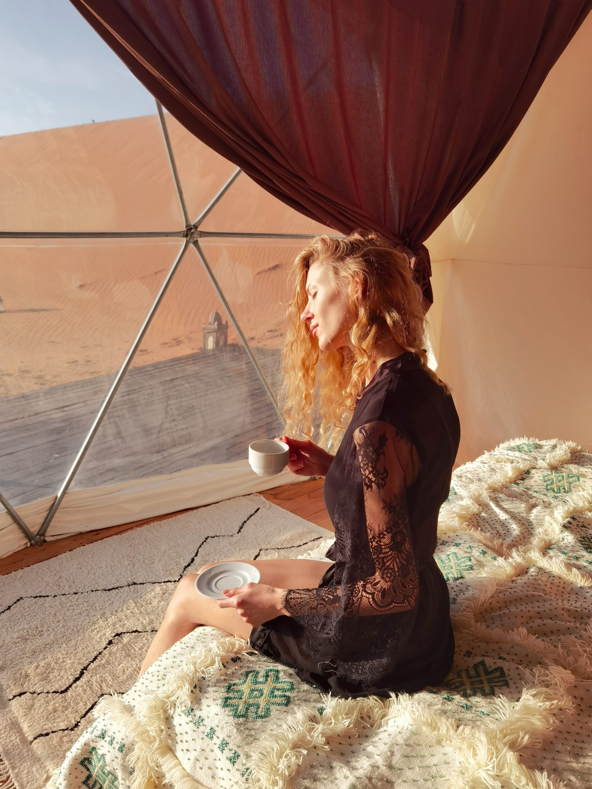 A young model enjoy her coffee in a dome tent at sunrise facing the Sahara Desert