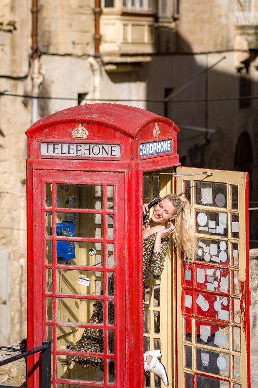 Blond girl smiling in a red telephone booth