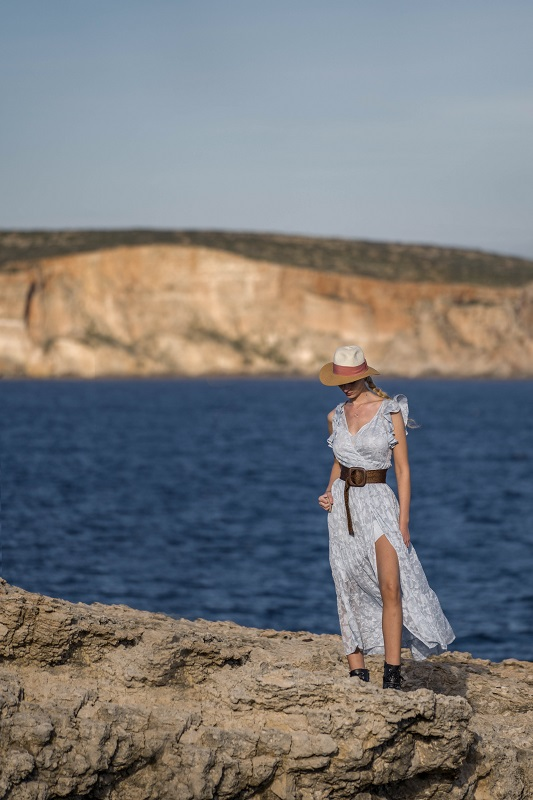 Blond women in a dress with a hat on the edge facing the sea