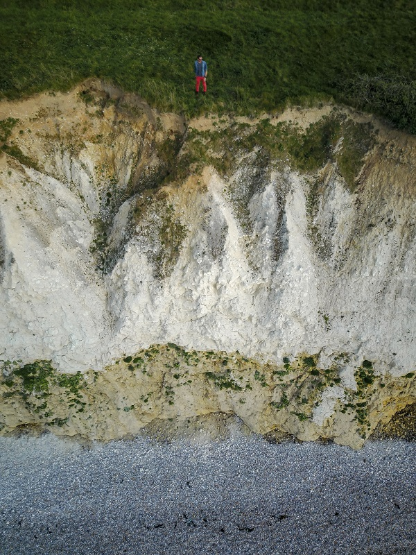 A man stands by the chalk cliff in North France