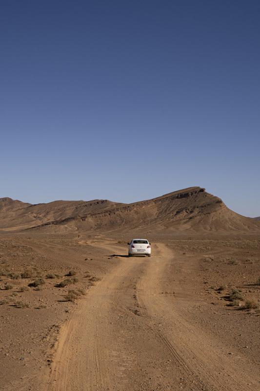 White rental sedan car driving on an arid off road path among African desert