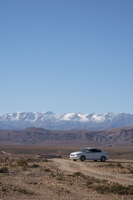 White Sedan car in front of the snow capped Atlas mountain in Morocco