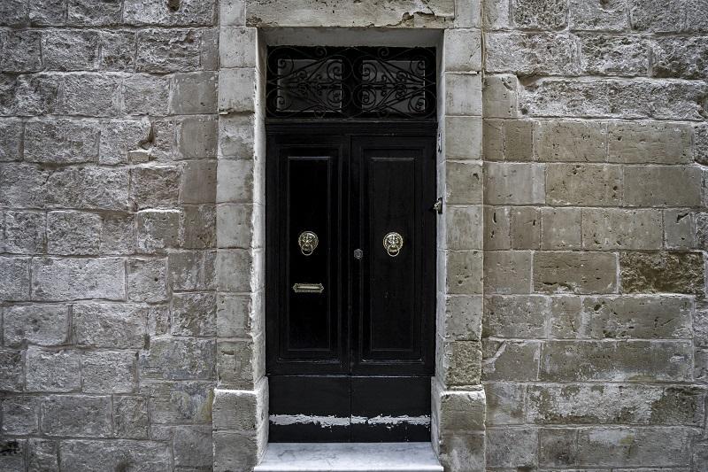Dark door Facade In Malta, typical stone wall