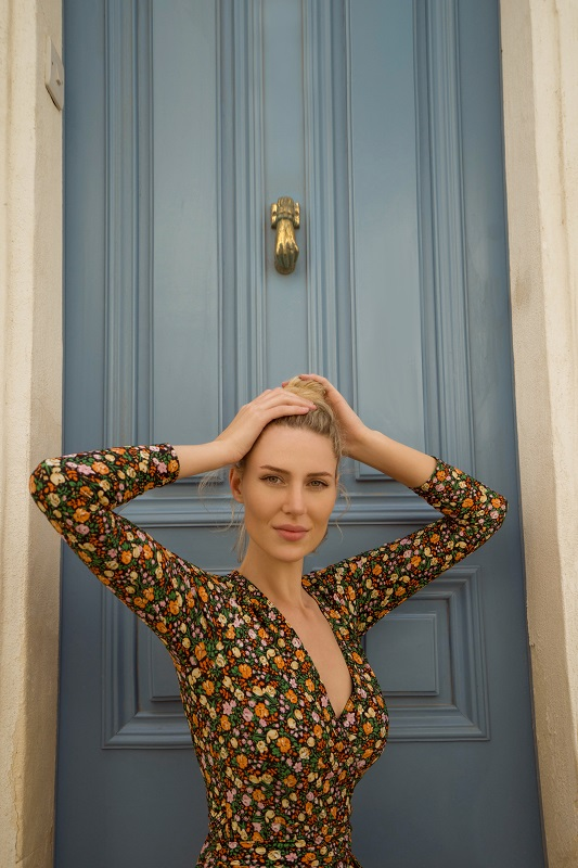 Beautiful woman in front of a colorful door in Malta