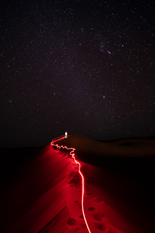 Nightscape, Sahara desert, a light trail lead to a man standing on a sand dune