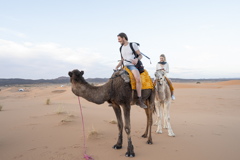 A happy tourist couple riding camels in the Sahara desert