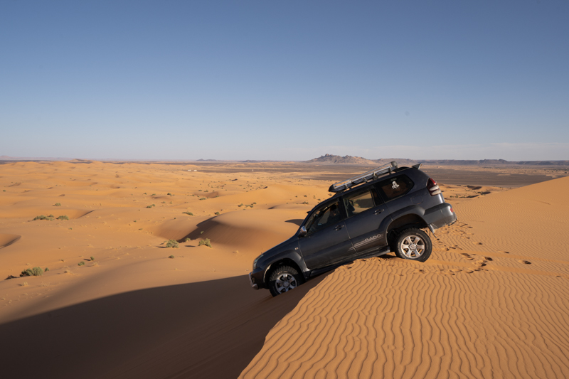 Scary 4wd stuck at the top of a desert dune, part of a tourist tour