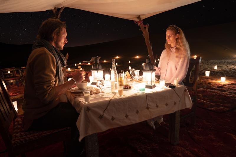 A young couple enjoy a romantic outdoor candlelight dinner in the Sahara desert