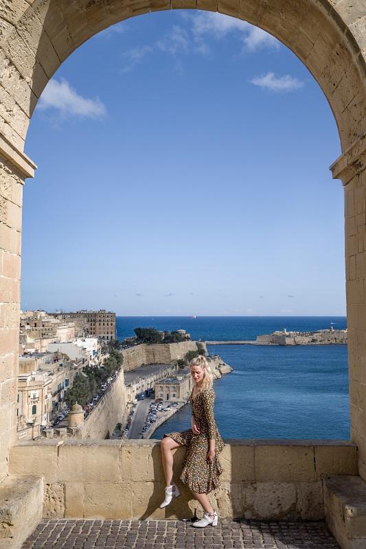 Girl sitting in the garden overlooking the sea in Malta