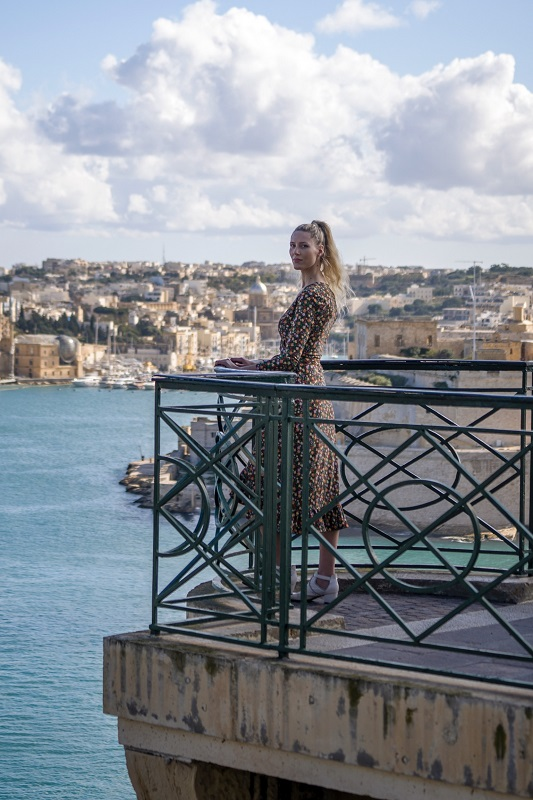 Girl standing on a balcony overlooking the harbor in Malta