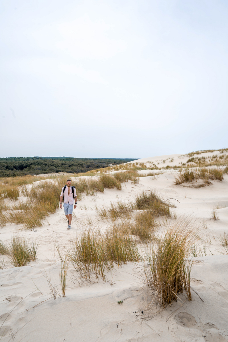 Man walks among arid dunes landscape