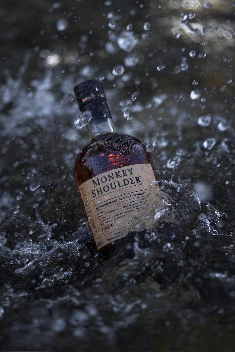 Monkey Shoulder blended malt whisky bottle in water, product photography