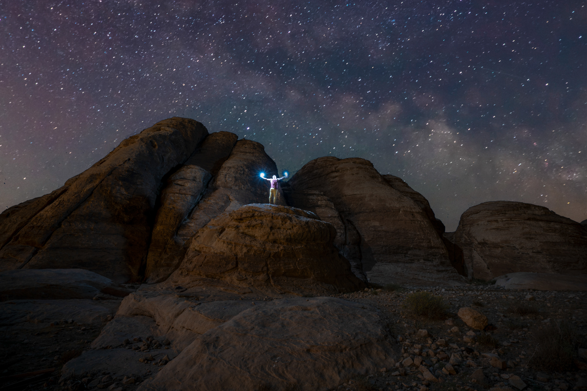Man on top of a rock faces Milky way