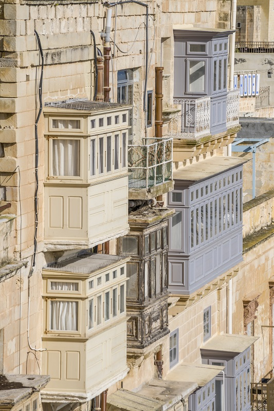 Traditional Maltese Balconies on a facade, stone wall and Maltese architecture
