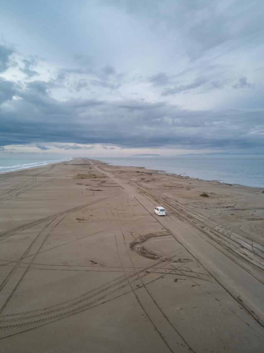 Camper van on a beach at sunrise, drone portrait