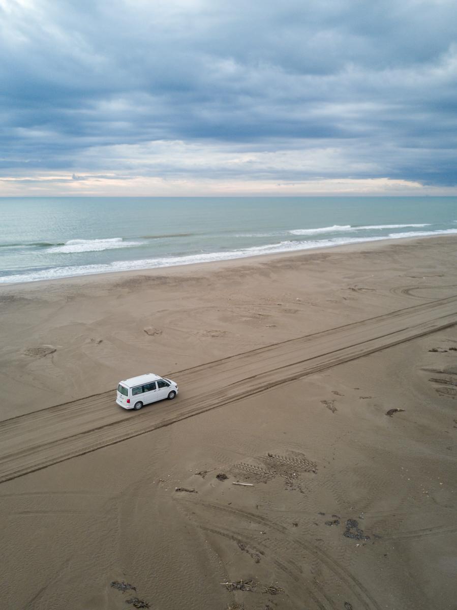Van driving a long infinite sandy road