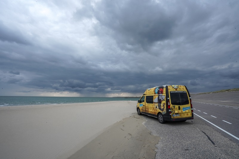 Campervan parked by the North Sea on a stormy day