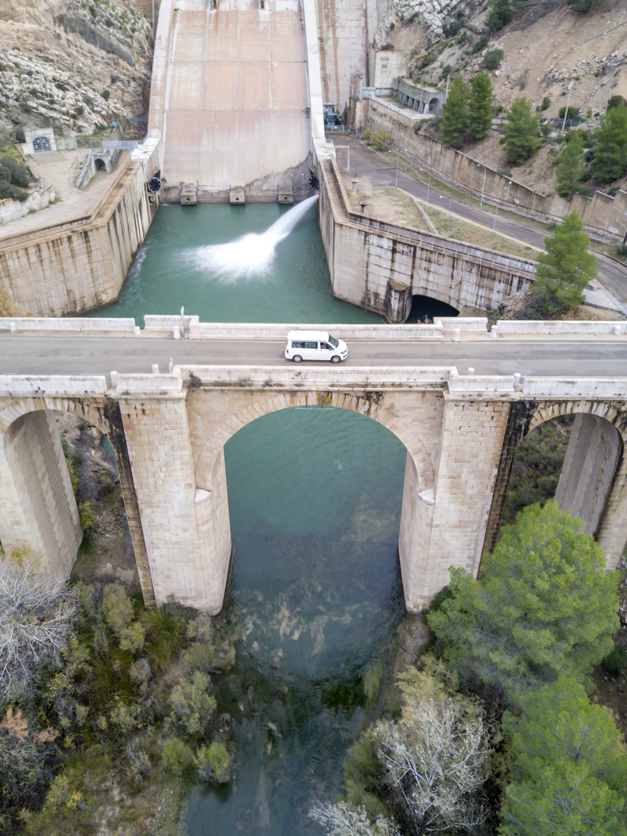 Camper van on a bridge over a dam, drone aerial