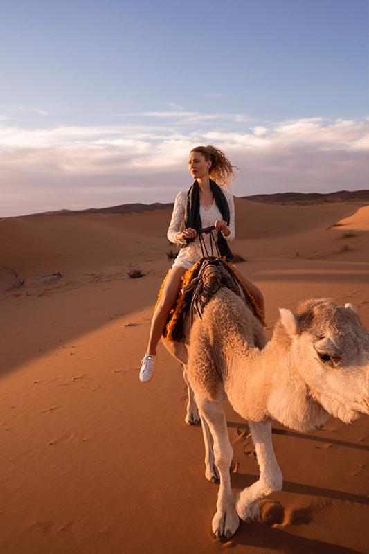 An attractive young woman riding a camel, Morocco Sahara desert