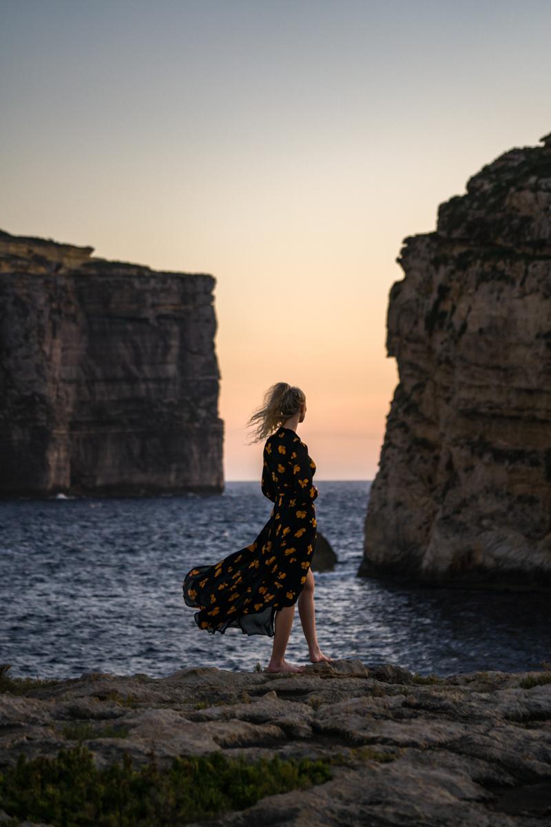 Woman in dress by at sunset in Malta,Dwejra Bay