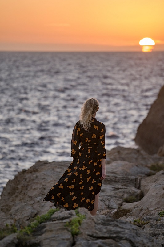 Woman standing near a cliff in front of the mediterranean sea