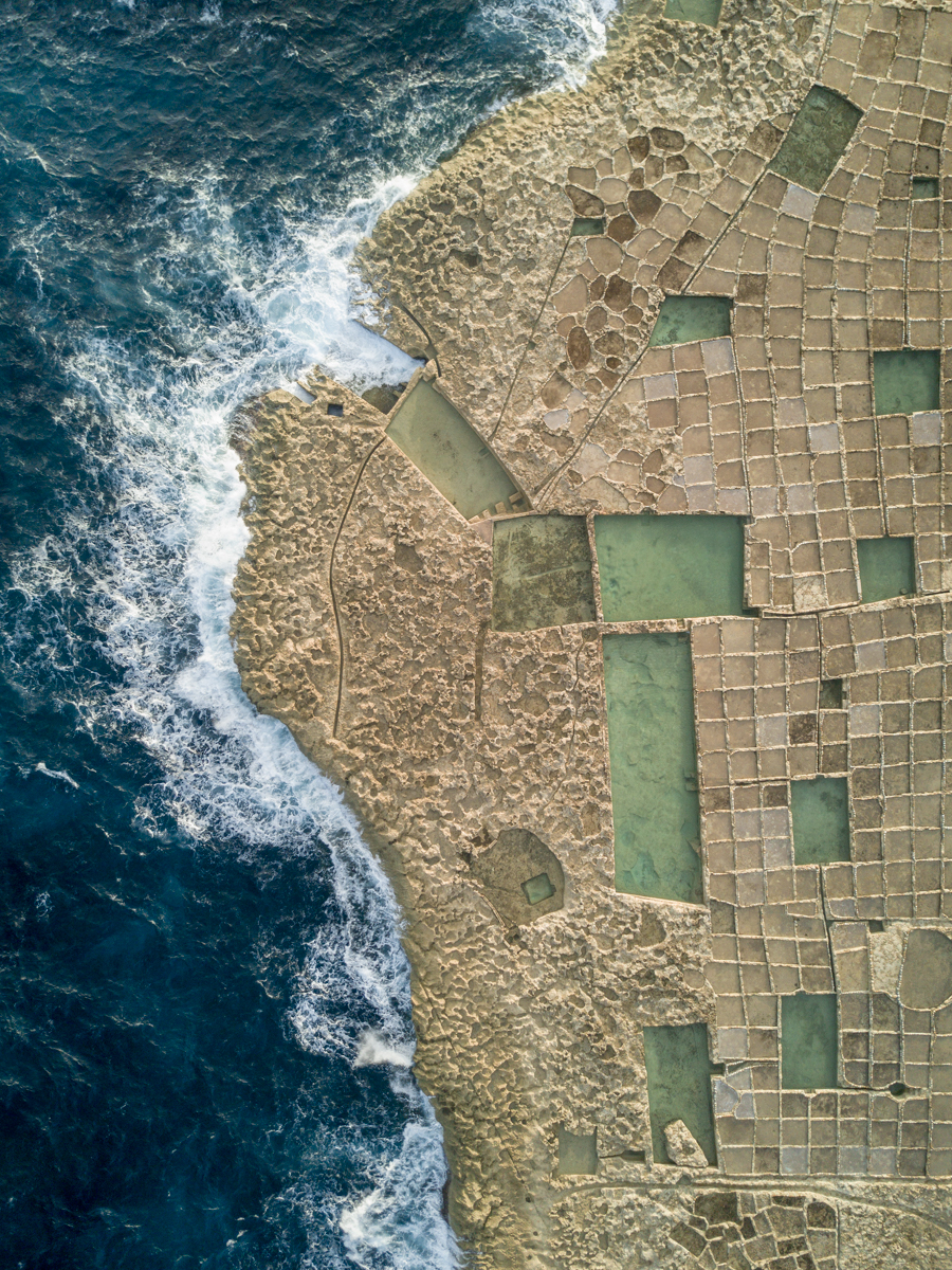 Carved salt pan in Malta by the sea, aerial drone